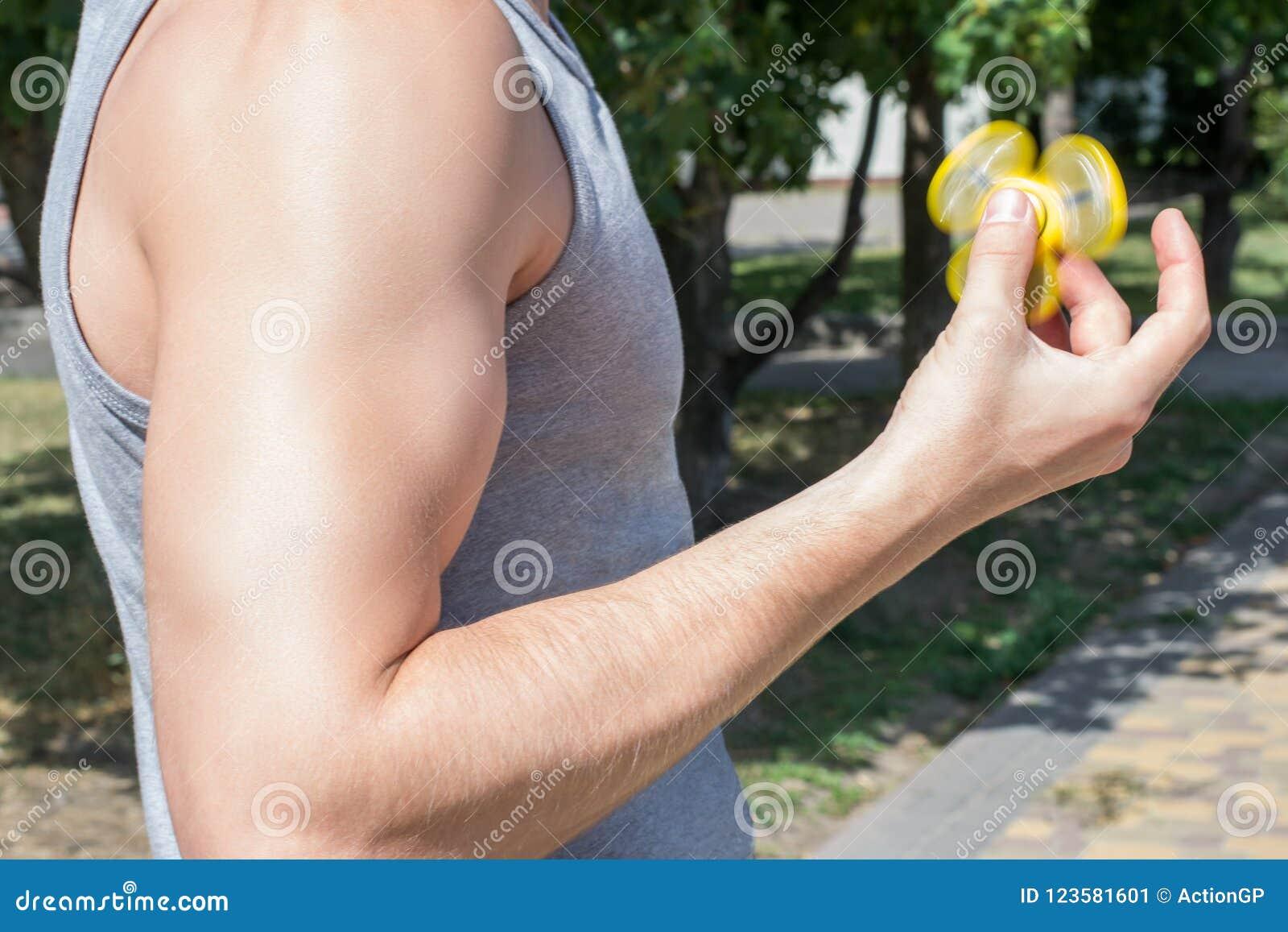 Фото сильного человека играя обтекатель втулки непоседы пока имеющ hol игрока gamer парня прогулки сексуальный мышечный красивый