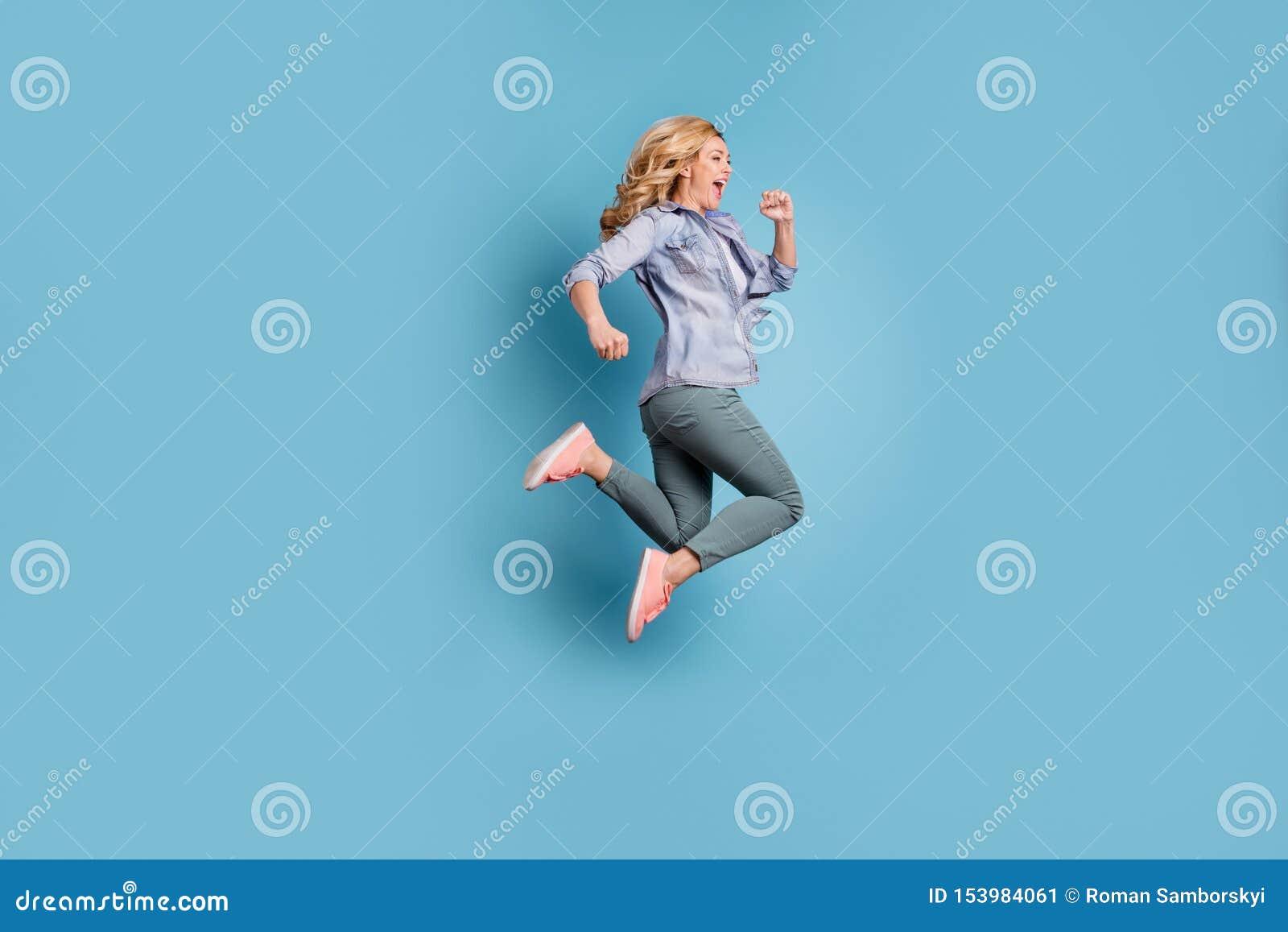 Фото стороны профиля полнометражное услаженных брюк брюк человека крича нося изолированных над голубой предпосылкой