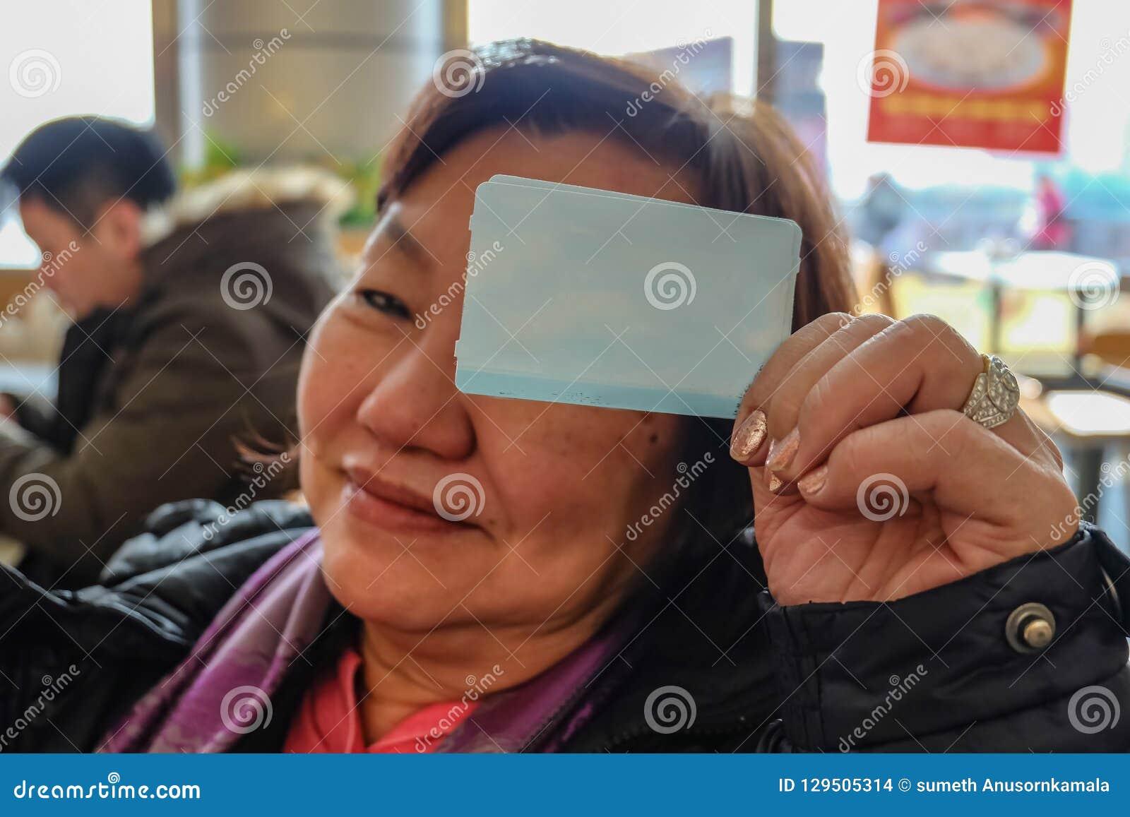 Фото Defocus старых азиатских женщин делает шоу cutie его билет на поезд