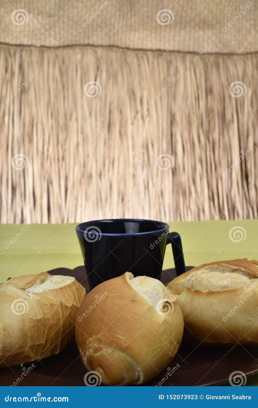 Французский хлеб, на плите с черной чашкой в предпосылке