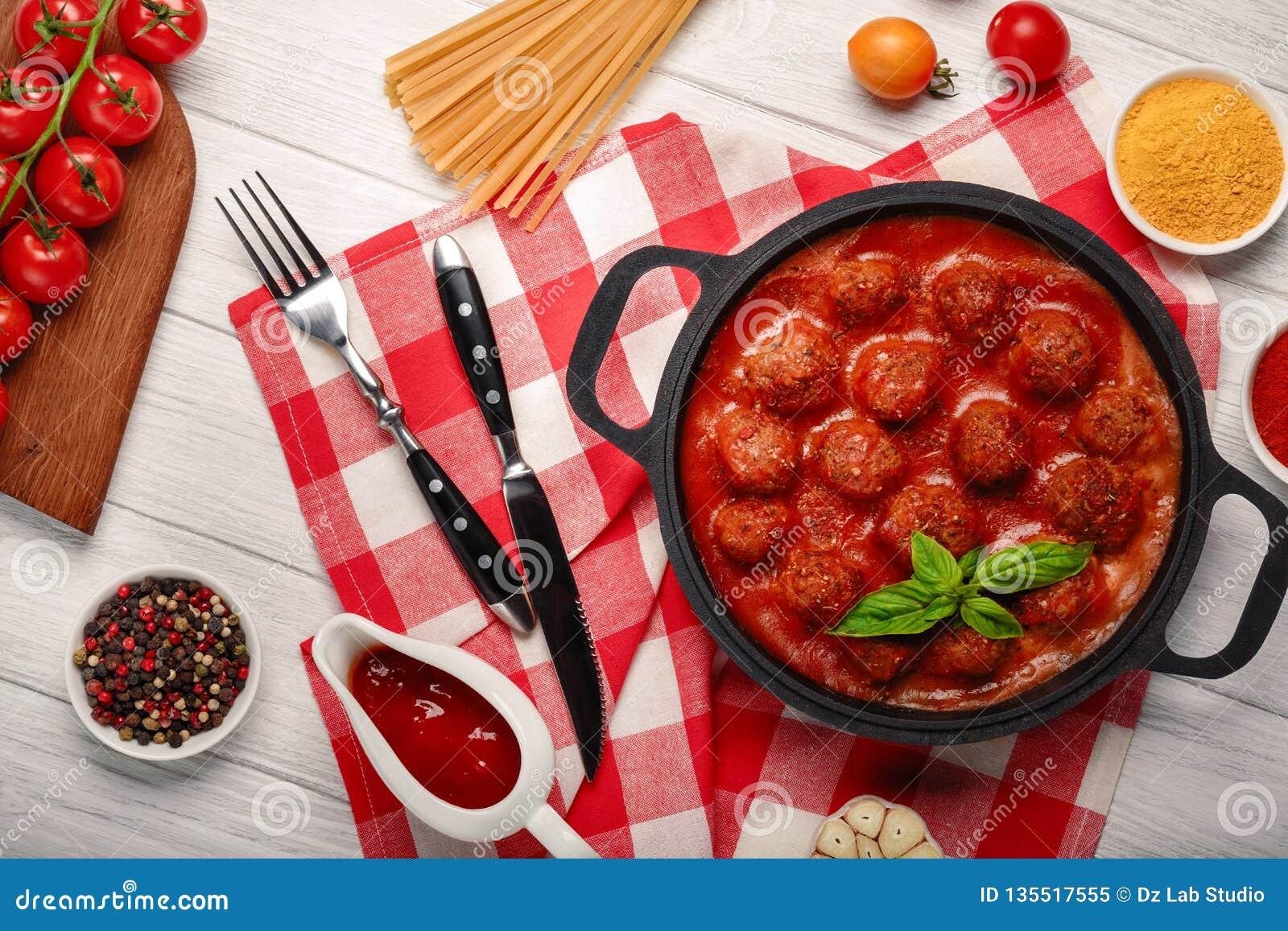 Фрикадельки в томатном соусе со специями в сковороде и томатах вишни на разделочной доске и белой деревянной доске