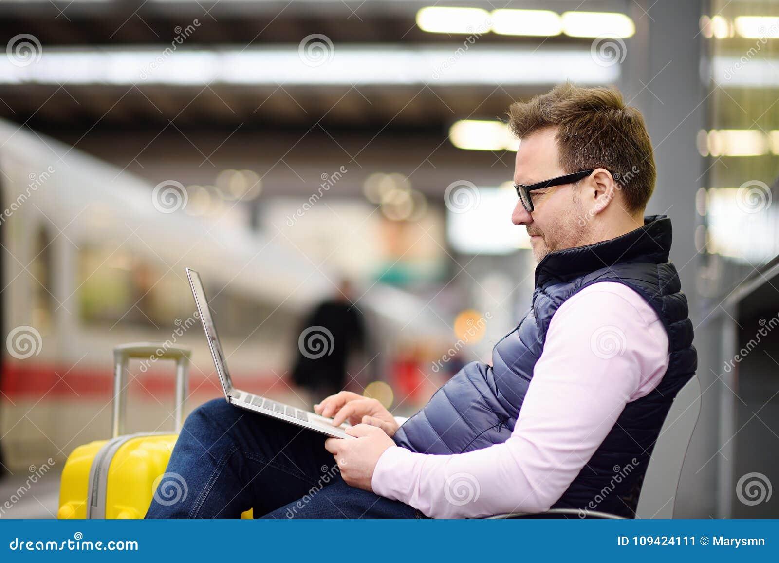 Фрилансер работая с компьтер-книжкой в вокзале пока ждет переход
