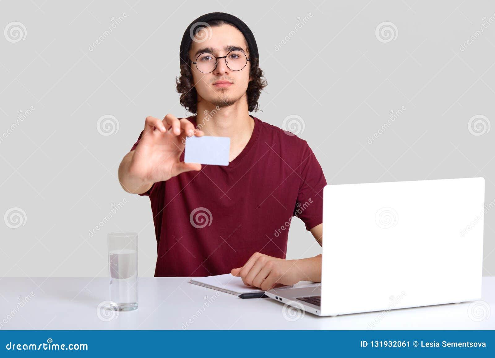 Фрилансер собственной личности уверенный мужской сидит на фронте раскрытого ноутбука, делает примечания, протягивает руку с пусто