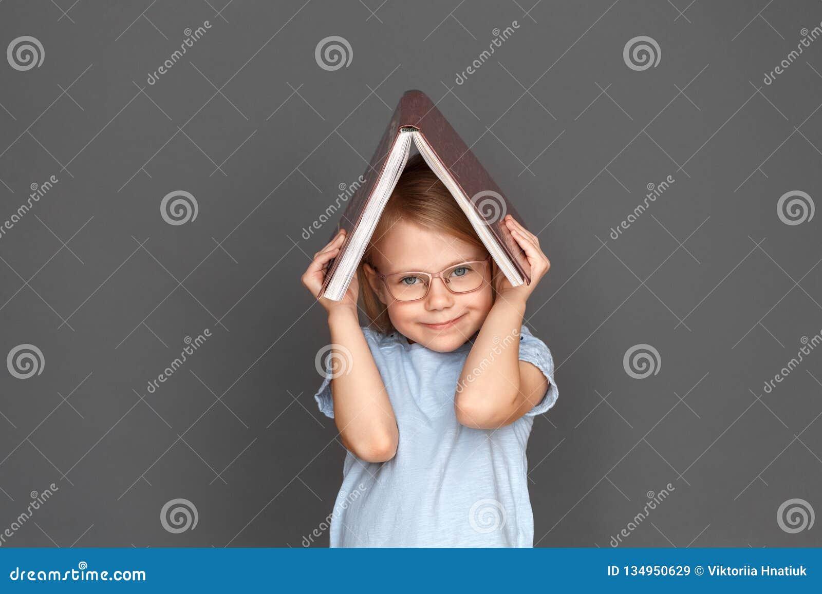 фристайл Маленькая девочка в eyeglasses на сером скрывании под усмехаться книги милый