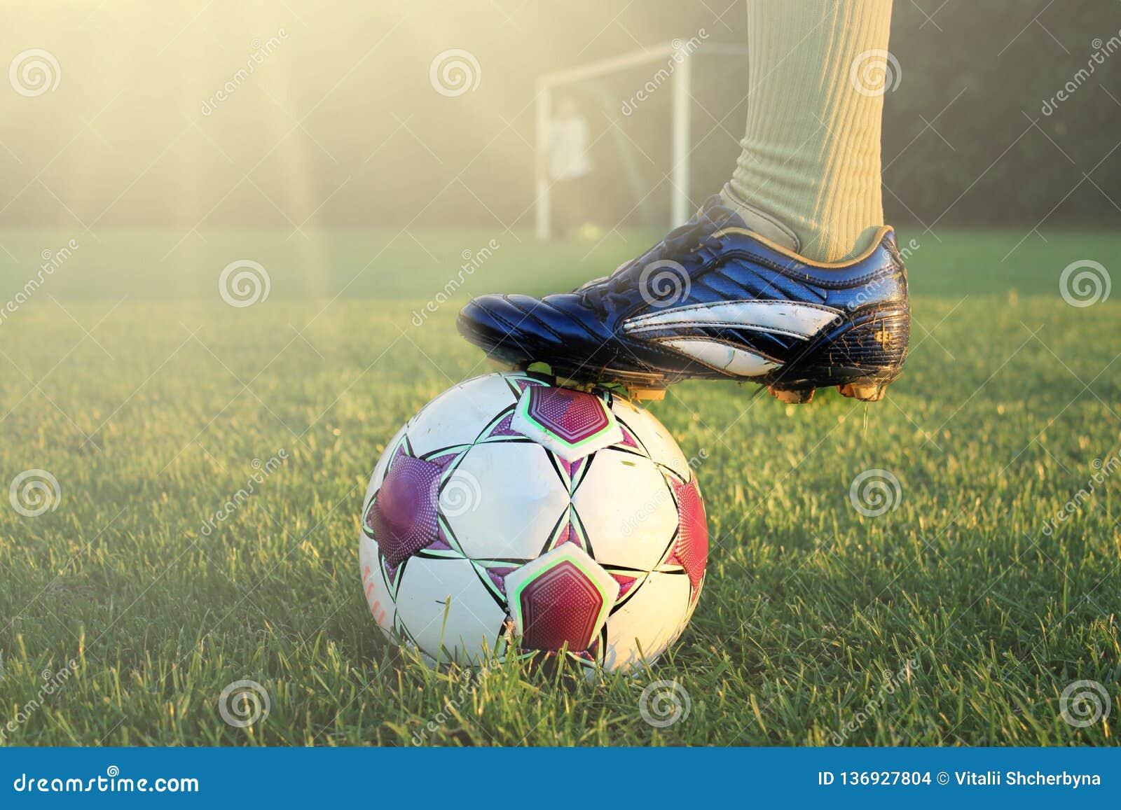 Футболист в действии с футболом в ярко освещенном внешнем стадионе Фокус на переднем плане и футбольный мяч с малой глубиной