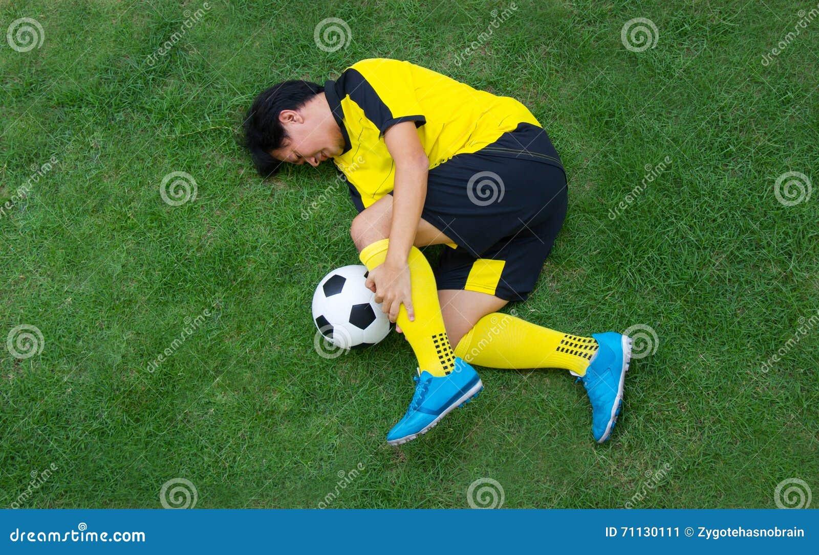Футболист в лежать желтого цвета раненый на тангаже