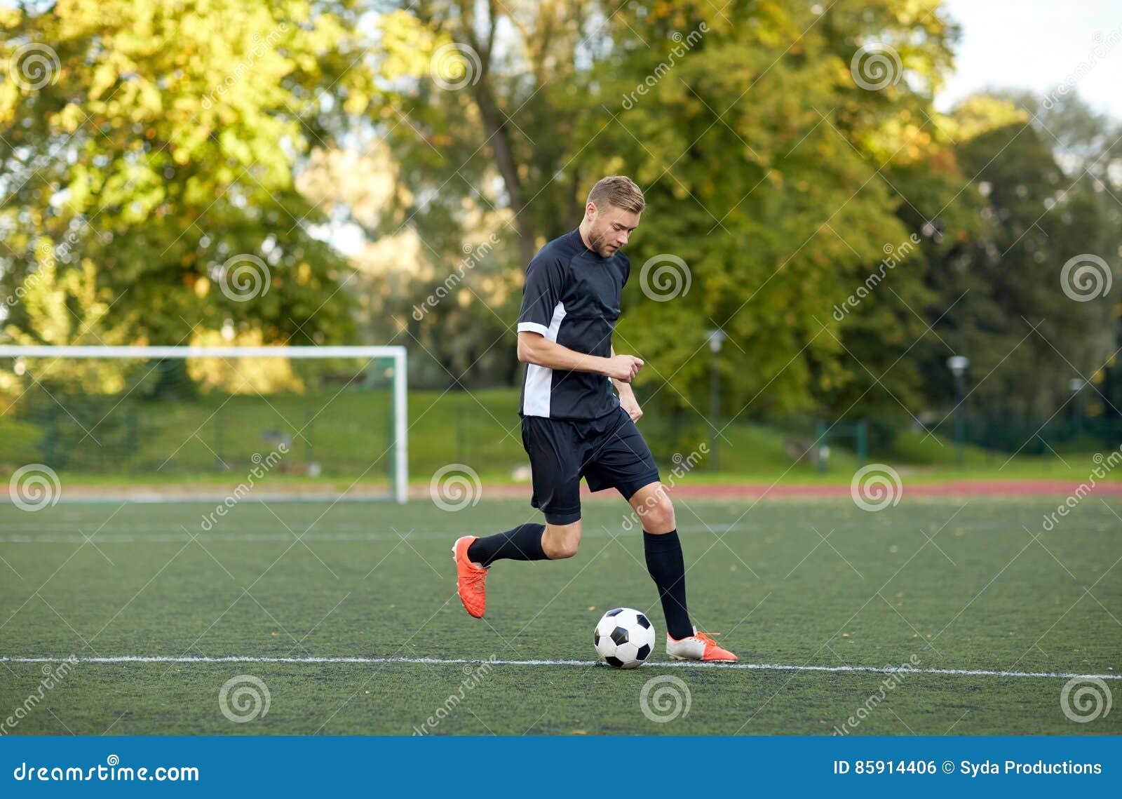 Футболист играя с шариком на футбольном поле