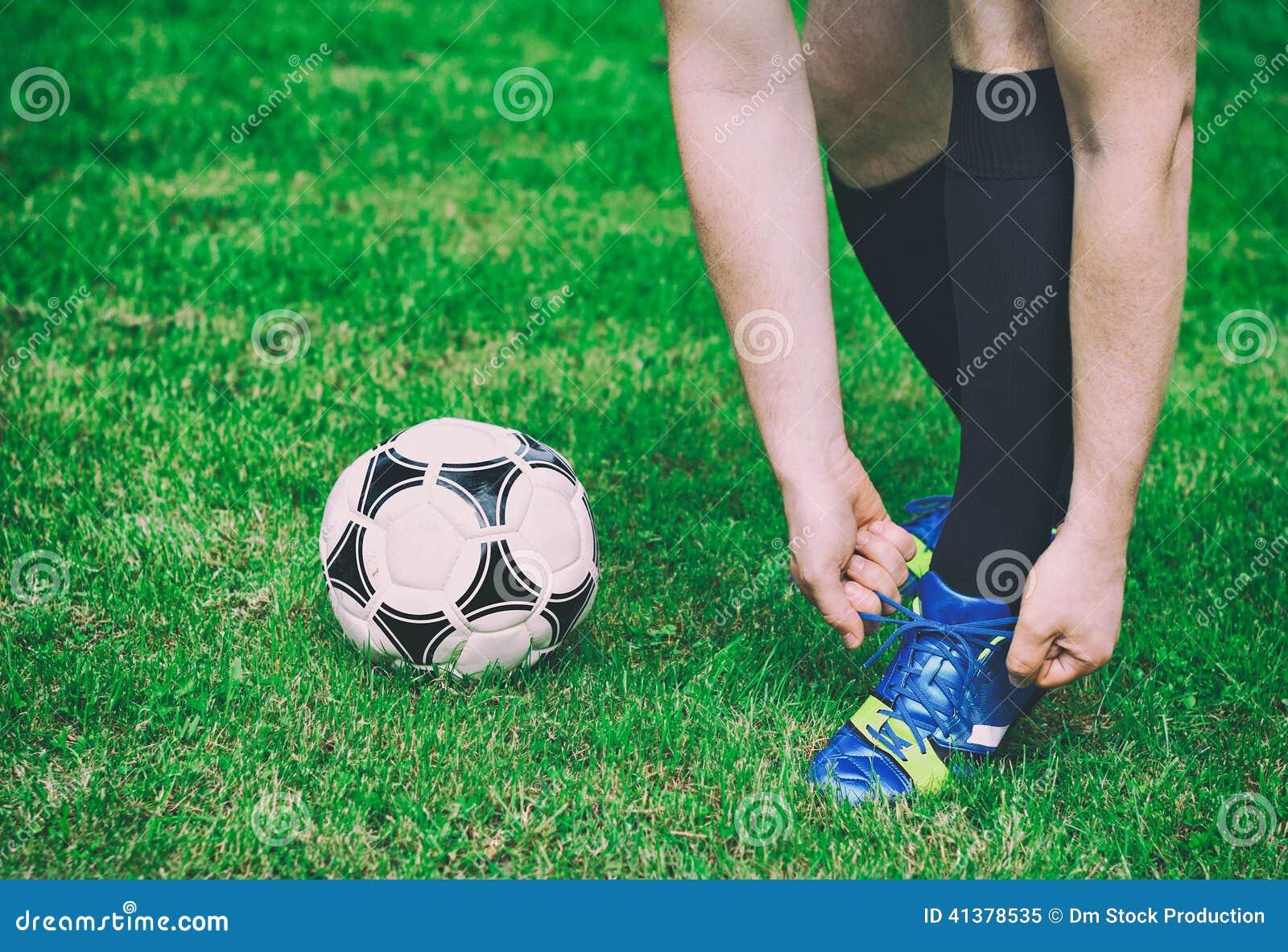 Футболист связывая его ботинки