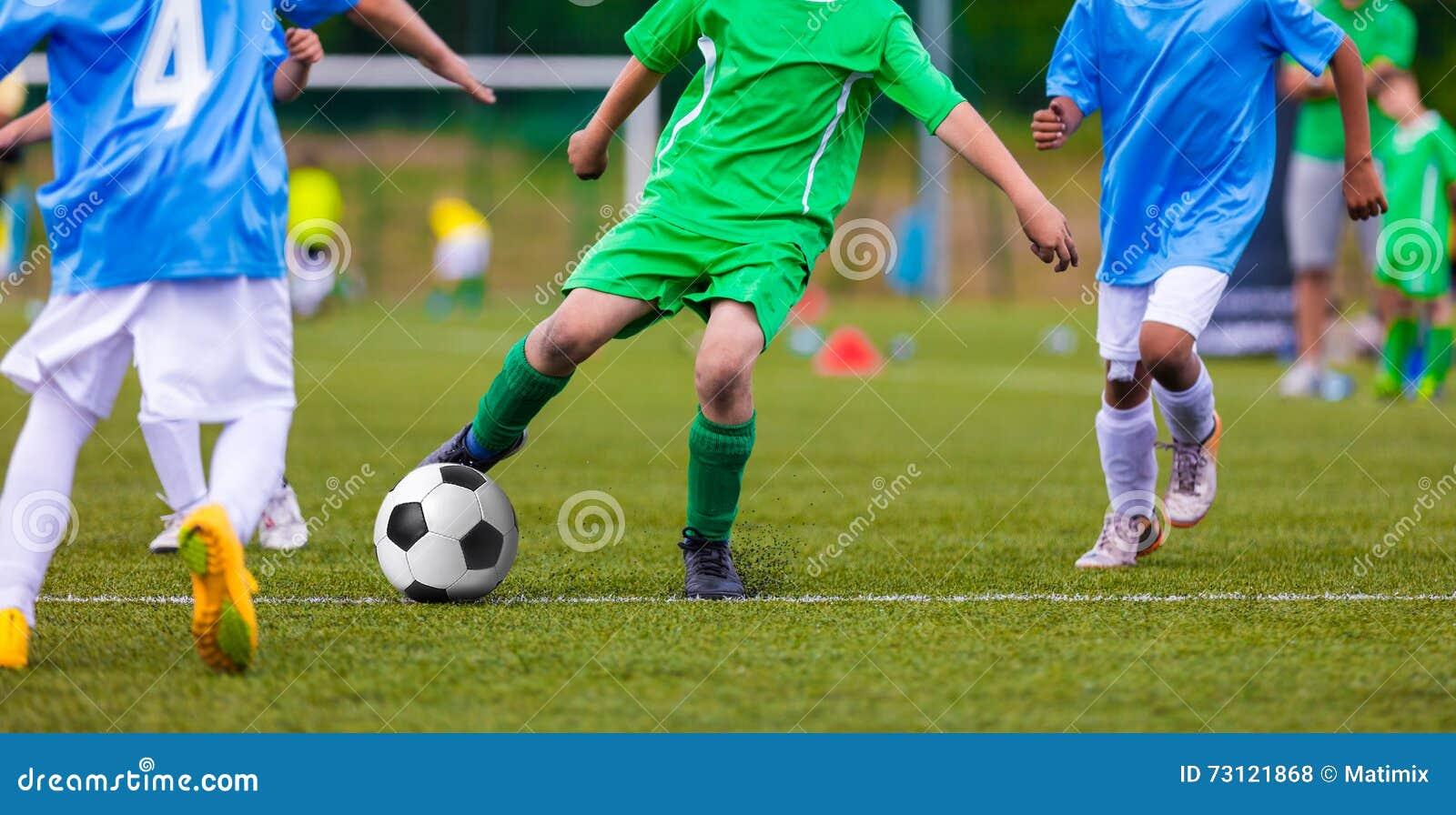 Футбольные команды футбола молодости пиная футбольный мяч на спортивной площадке