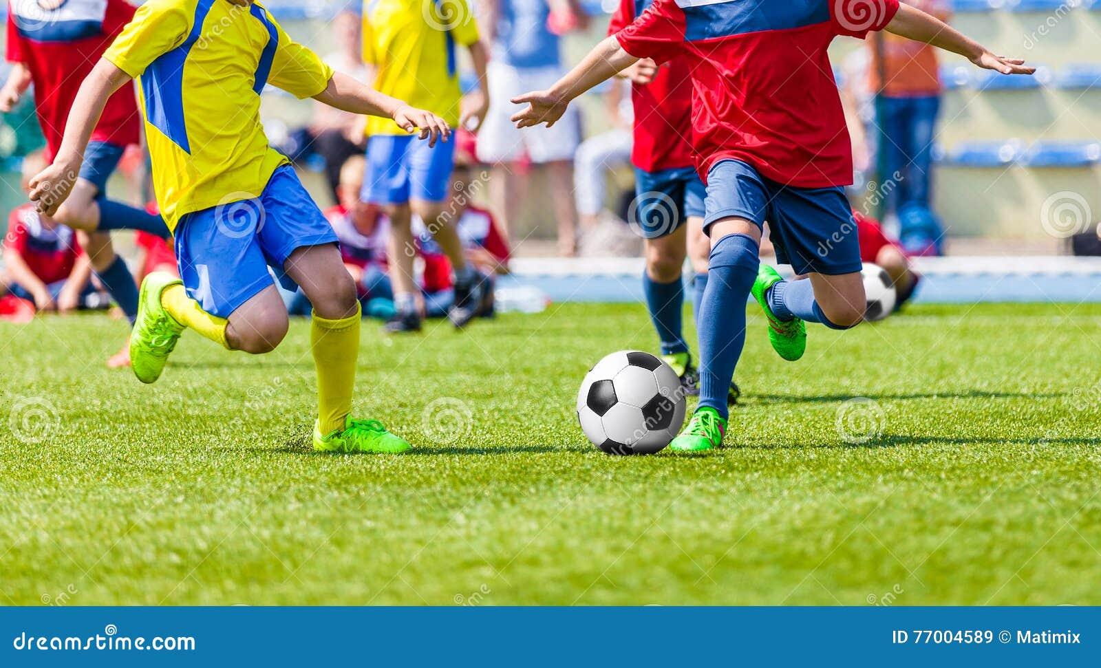 Футбольный матч футбола молодости Дети играя игру футбола на поле спорта