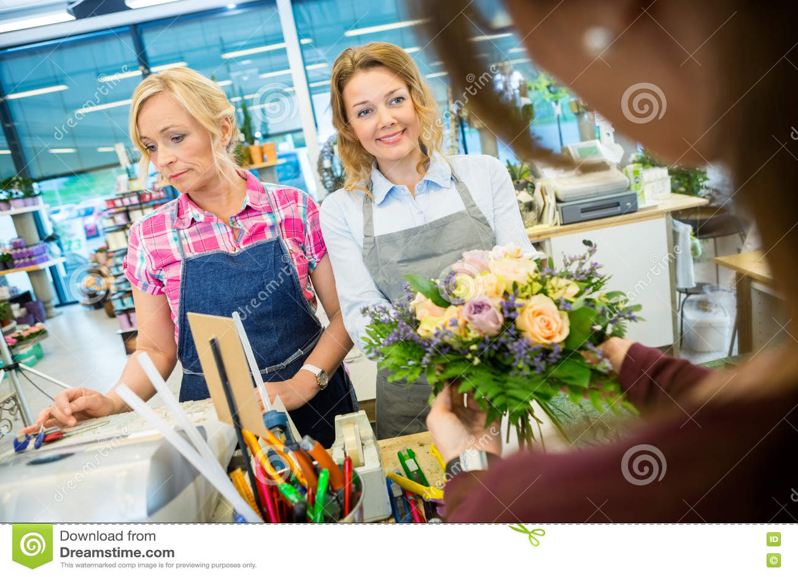Download Флористы продавая розовый букет к клиенту в магазине Стоковое Фото - изображение насчитывающей свеже, таможня: 72289534