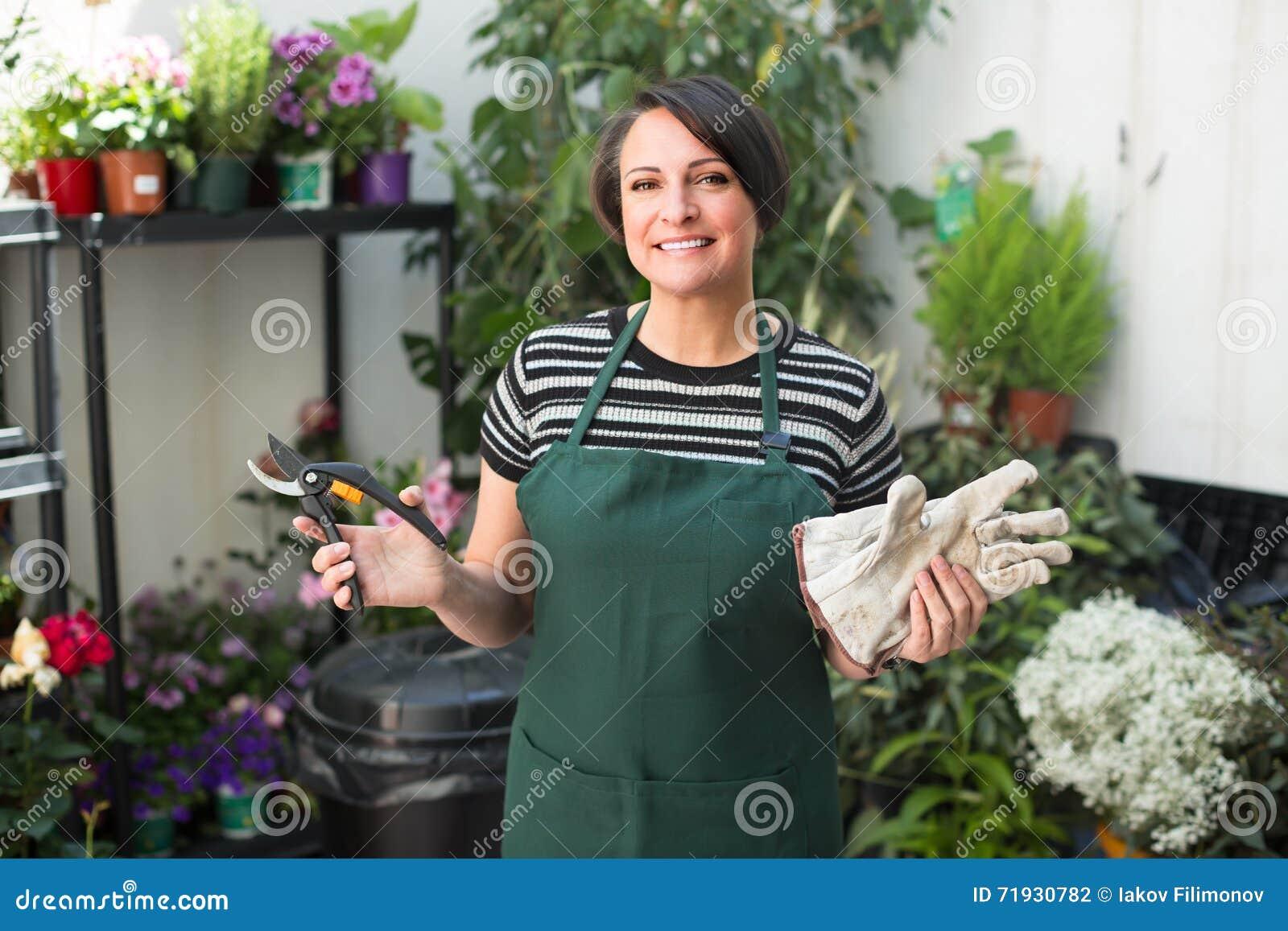 Флорист с инструментами в садовничая магазине