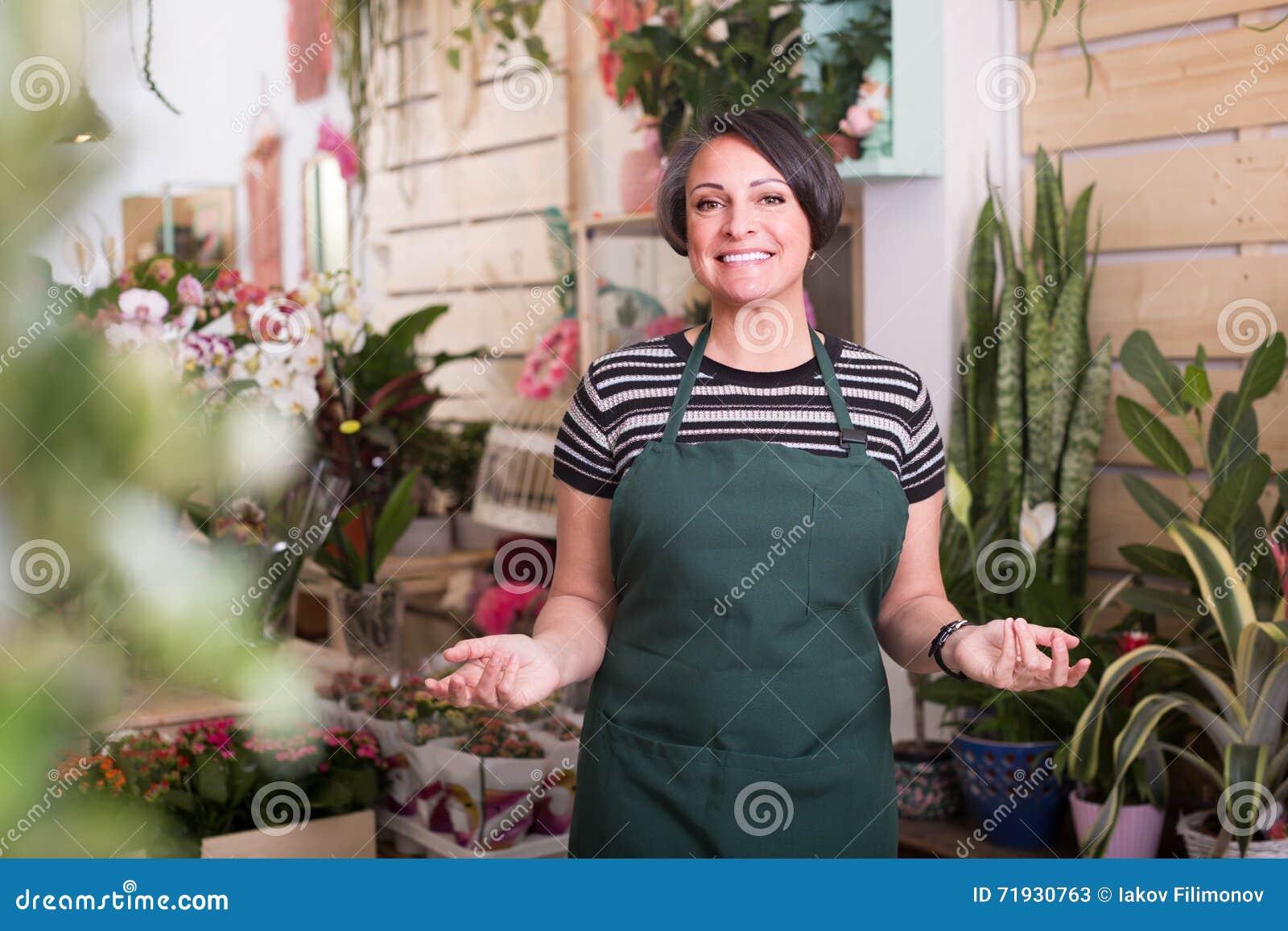 Флорист усмехаясь среди заводов