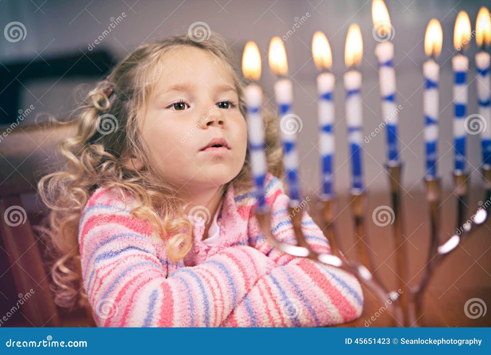 Ханука: Маленькая девочка смотрит свечи Хануки Lit