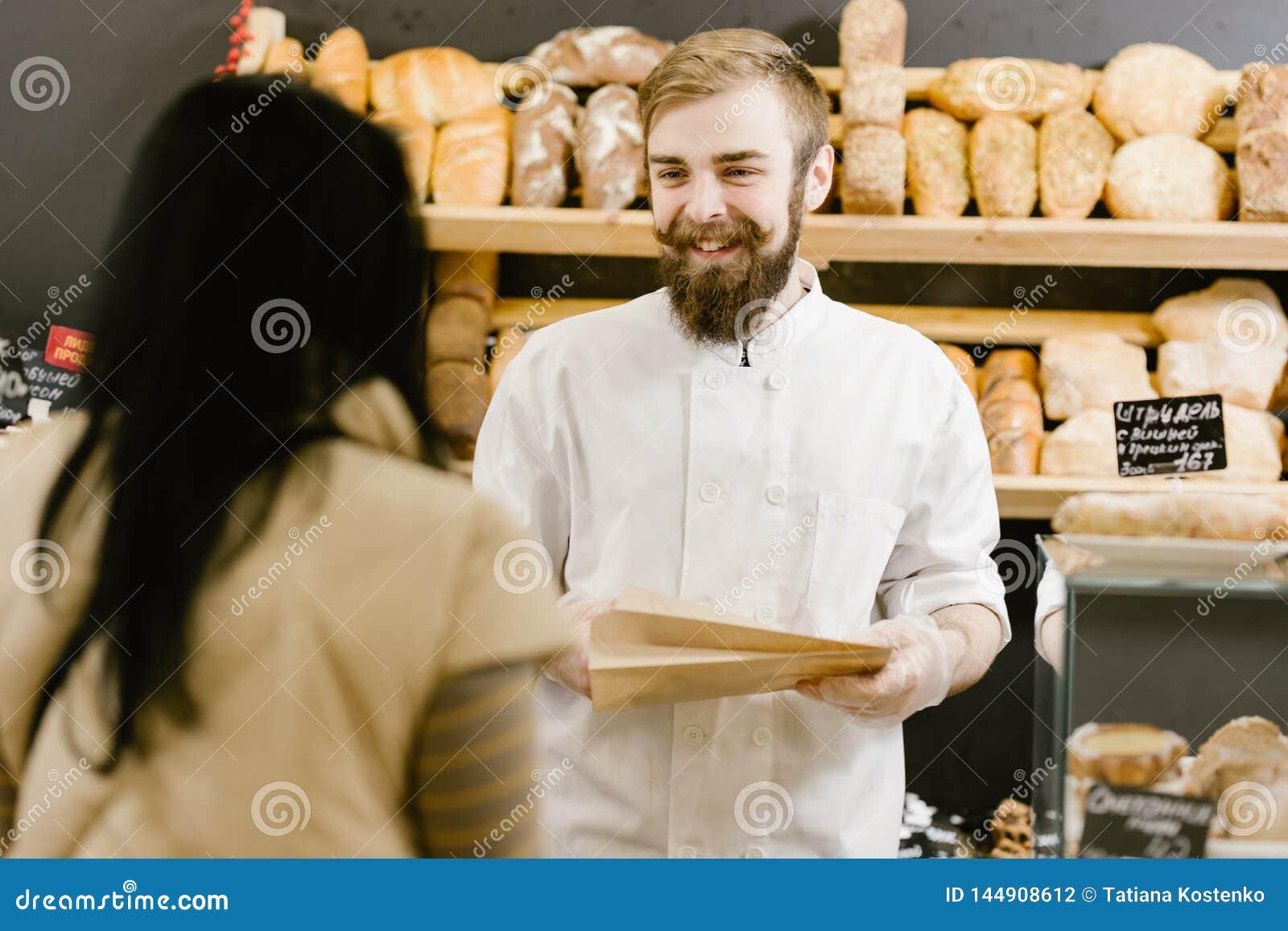 Харизматический хлебопек с бородой и усиком дает бумажный мешок хлеба клиенту в пекарне