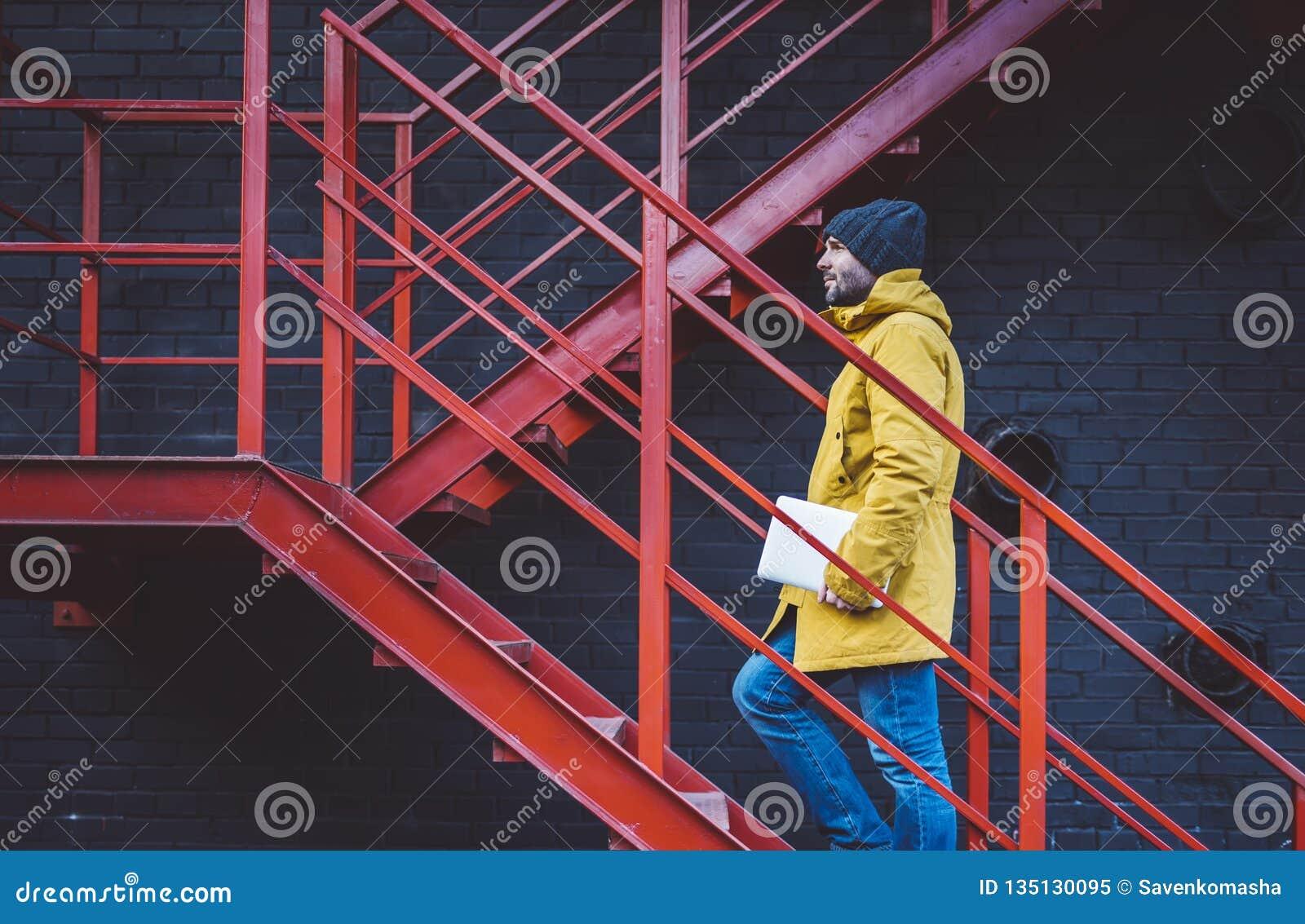 Хипстер с желтыми рюкзаком, курткой и крышкой поднимает на красную ретро лестницу с компьютером в руках, независимым держа ноутбу