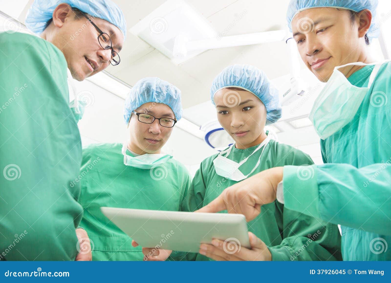 Хирурги используя таблетку для того чтобы обсудить метод работы