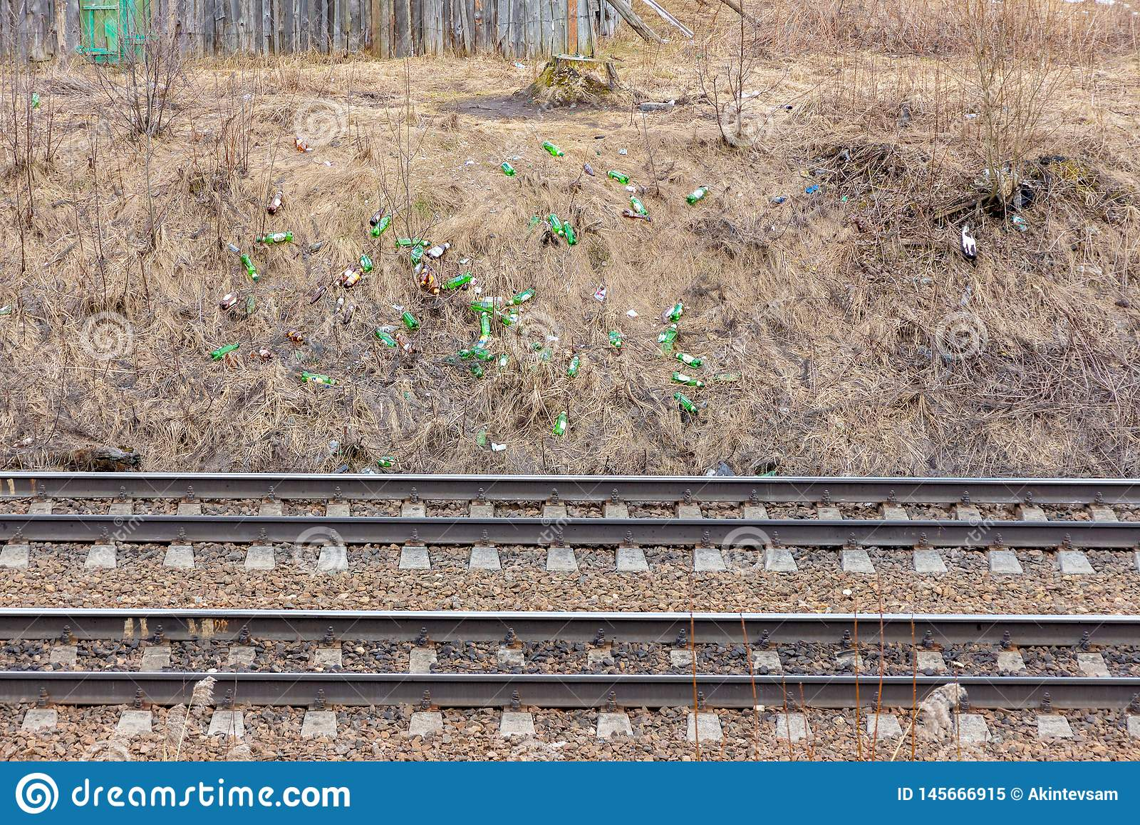Хлам железной дороги много стеклянных бутылок на железнодорожном обваловке