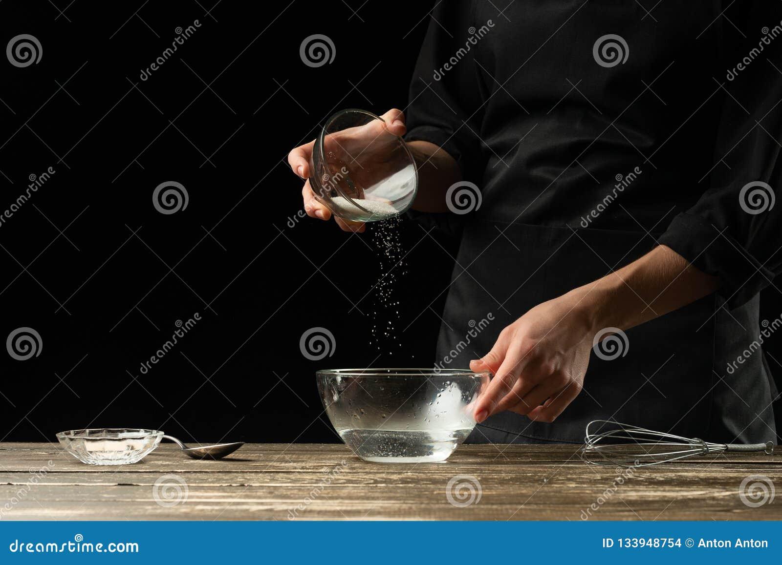 Хлебопек подготавливая тесто дрожжей, на темной предпосылке Подготовка концепции и теста пекарни