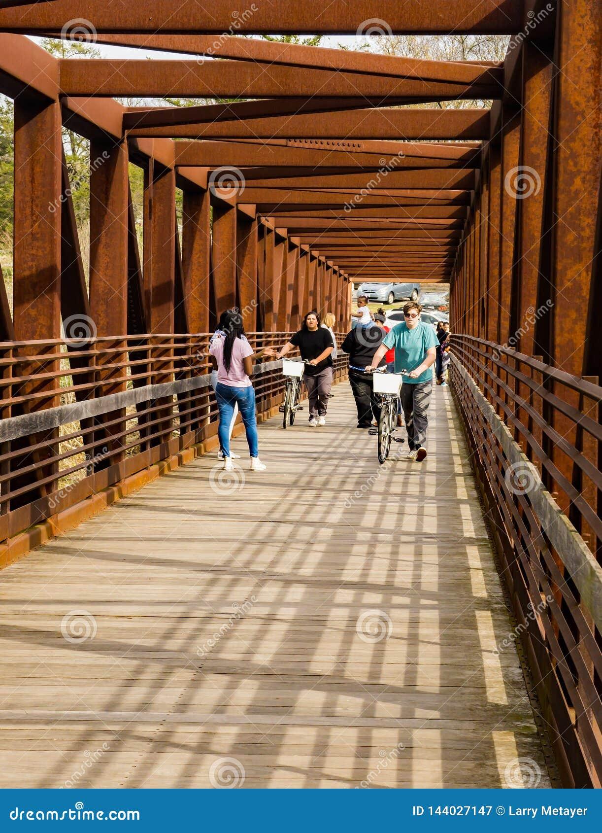 Ходоки пересекая мост металла на Greenway реки Roanoke