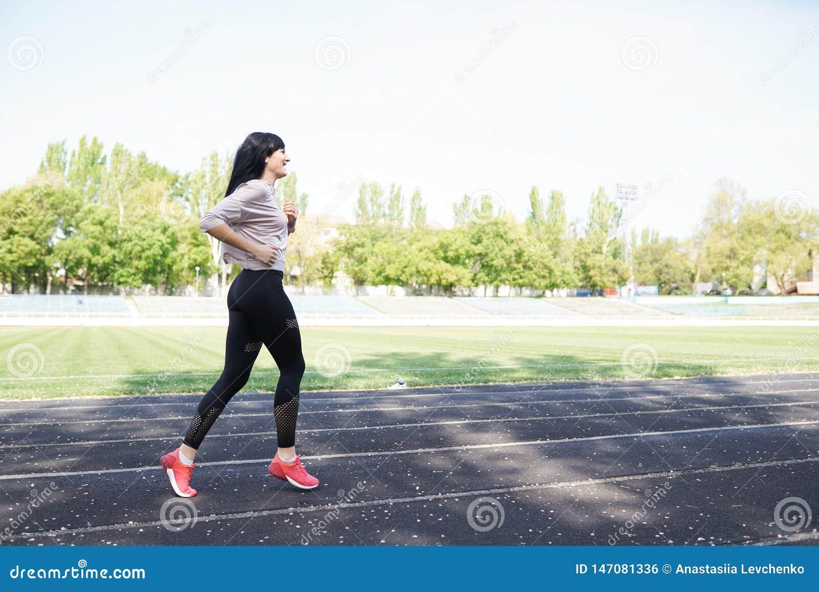 Ход молодой женщины во время солнечного утра на следе стадиона o o Sporty здоровая женщина