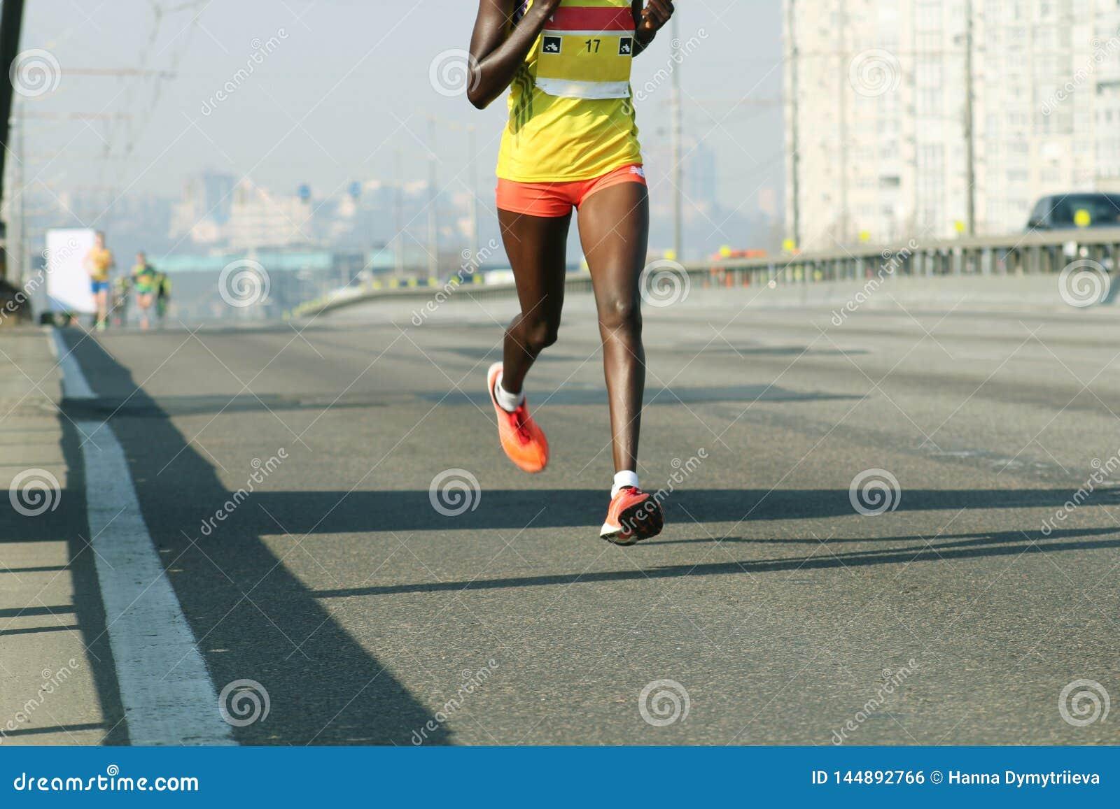 Ход молодой женщины на дороге моста города Ход марафона в свете утра Бег на дороге города Бег ног бегуна спортсмена