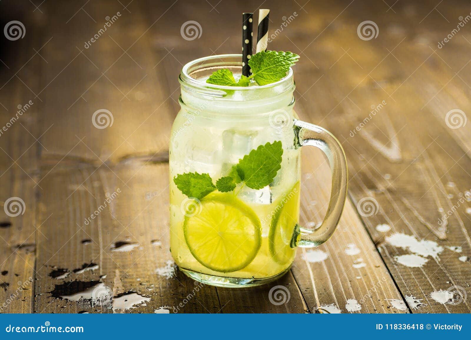 Холодный свежий коктеиль Mojito лимонада с листьями льда, лимона и мяты в опарнике каменщика