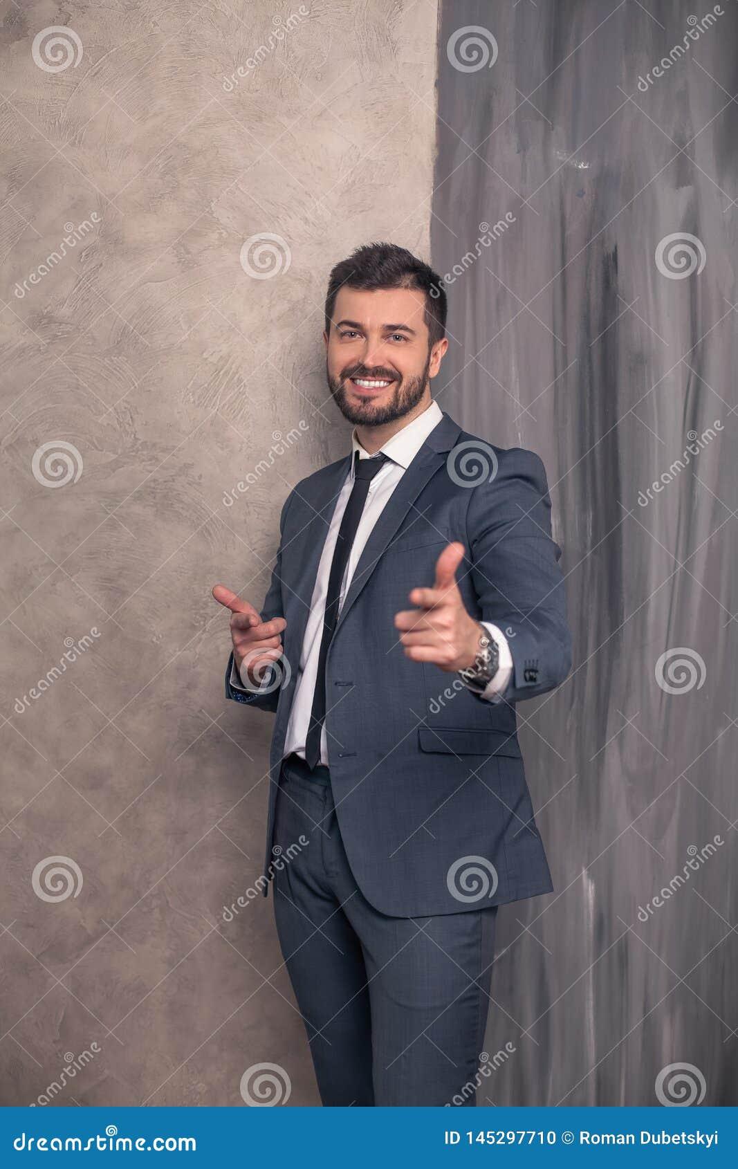 Хороший выглядя красивый счастливый бизнесмен стоит в его офисе указы