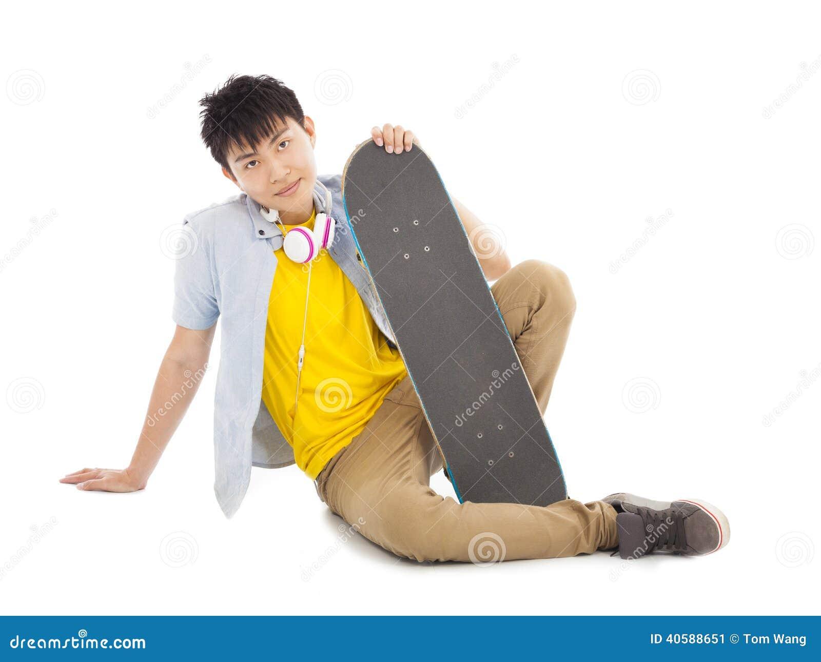 Холодный человек сидя и держа скейтборд