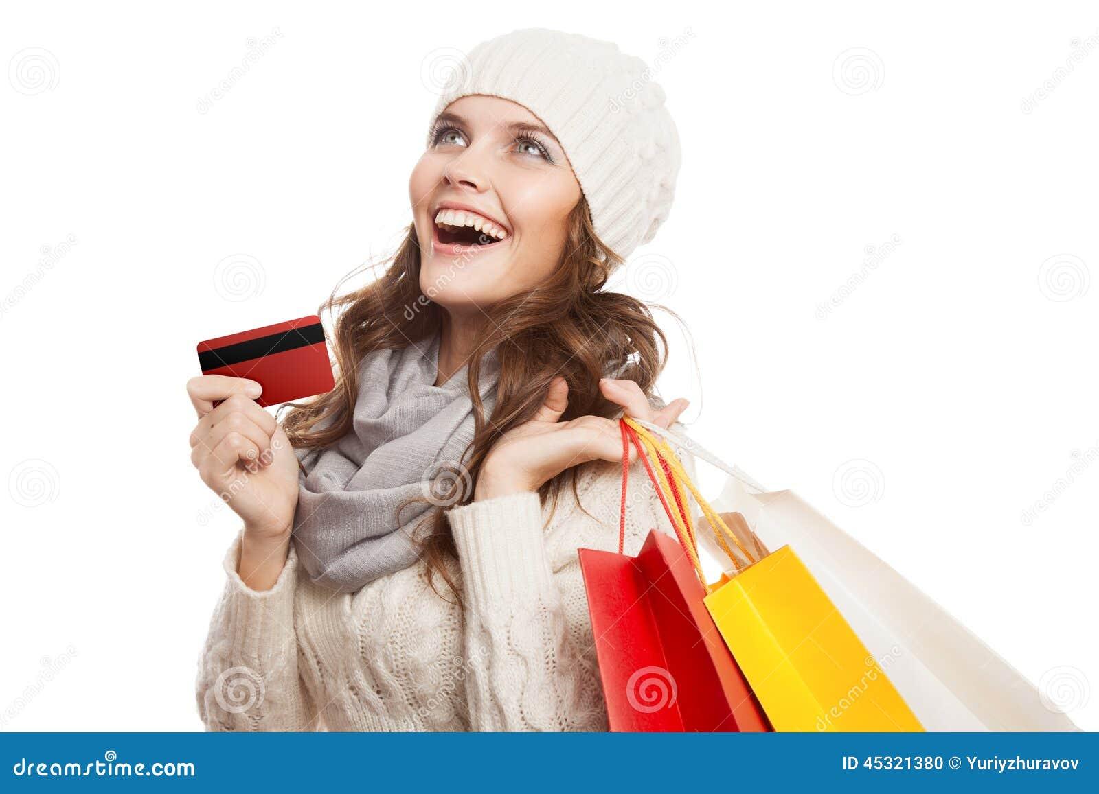 Ходя по магазинам счастливая женщина держа сумки и кредитную карточку Продажи зимы