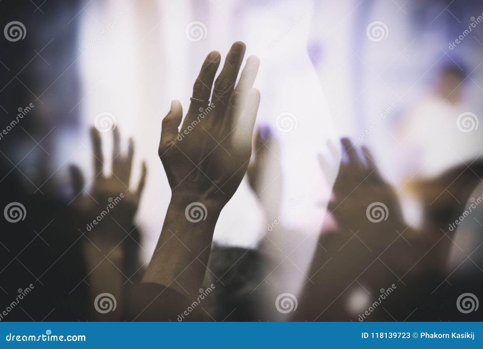 Христианское поклонение с поднятой рукой радостной в славе и влюбленности