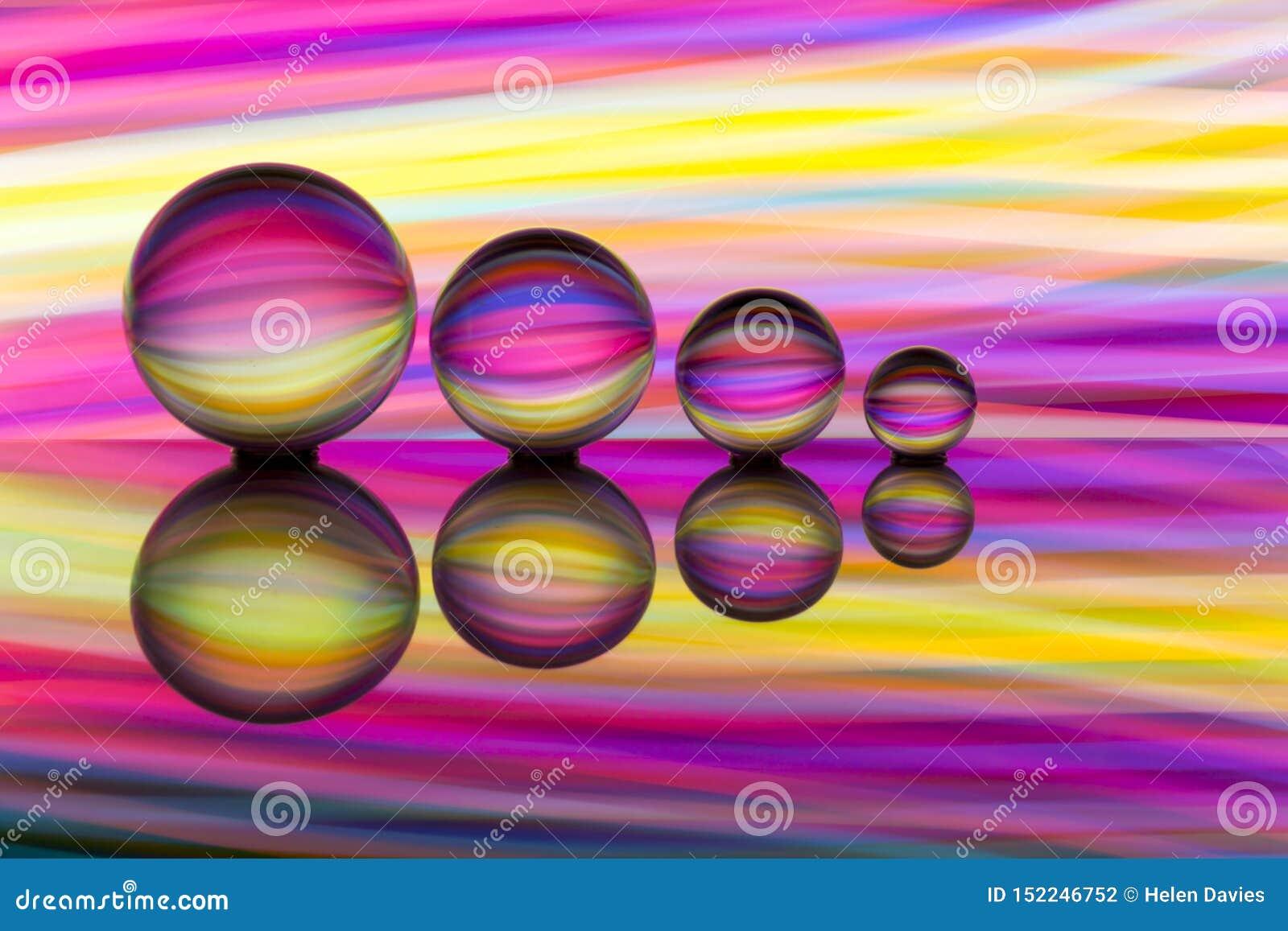 4 хрустального шара в ряд с красочными чертами цвета радуги за ими
