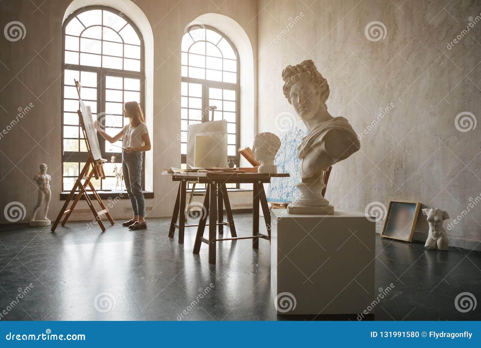 Художник девушки работая в комнате света мастерской Создание изображения Работа с красками, щетками и мольбертом творческо