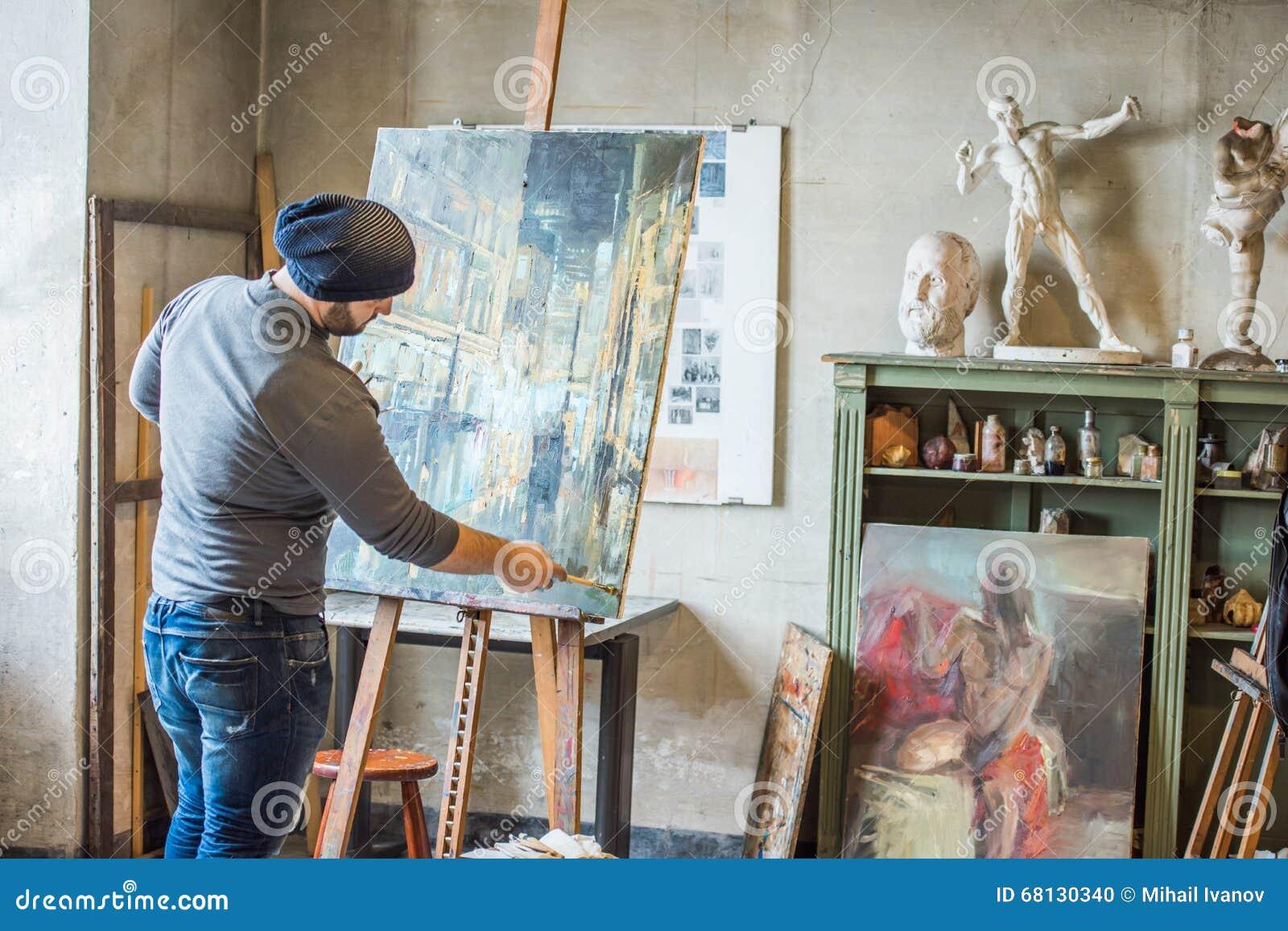 Художник в его картине студии с цветом масла