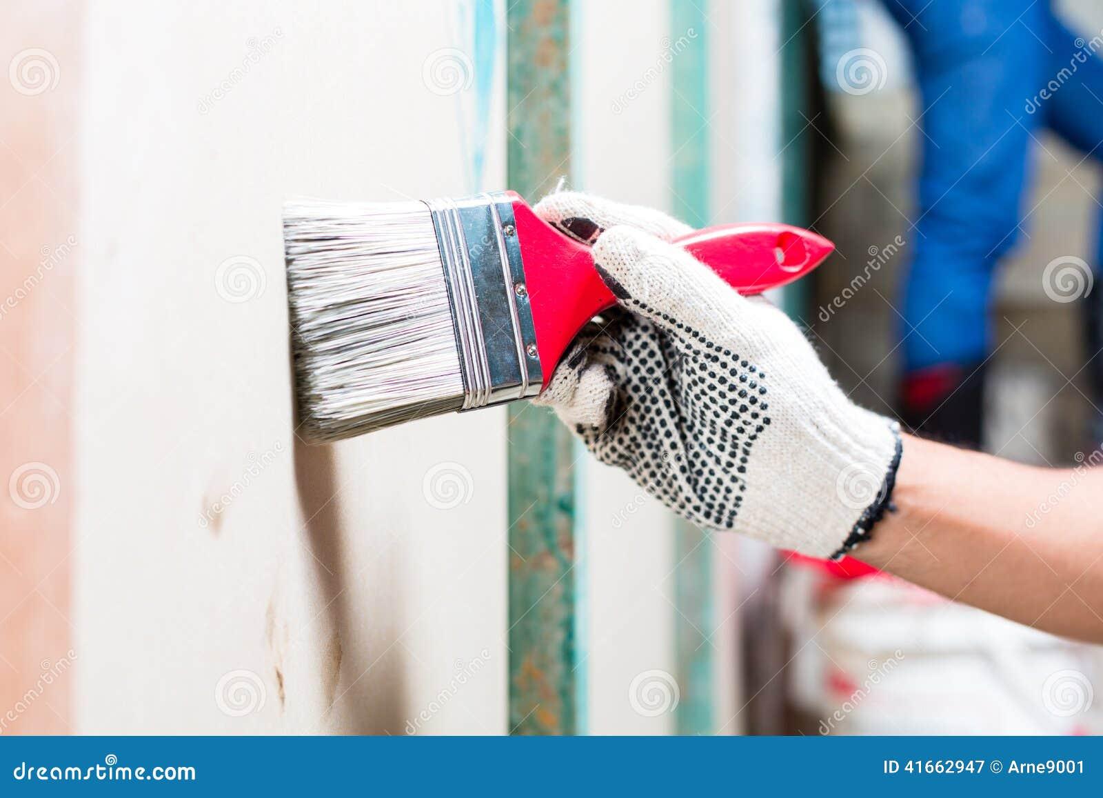 Художник с щеткой и краска на строительной площадке