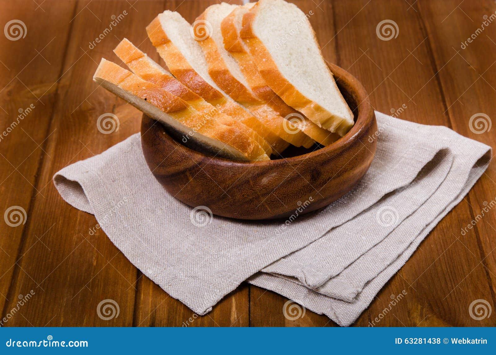 Хлеб отрезка стоит на linen салфетке в деревянном шаре
