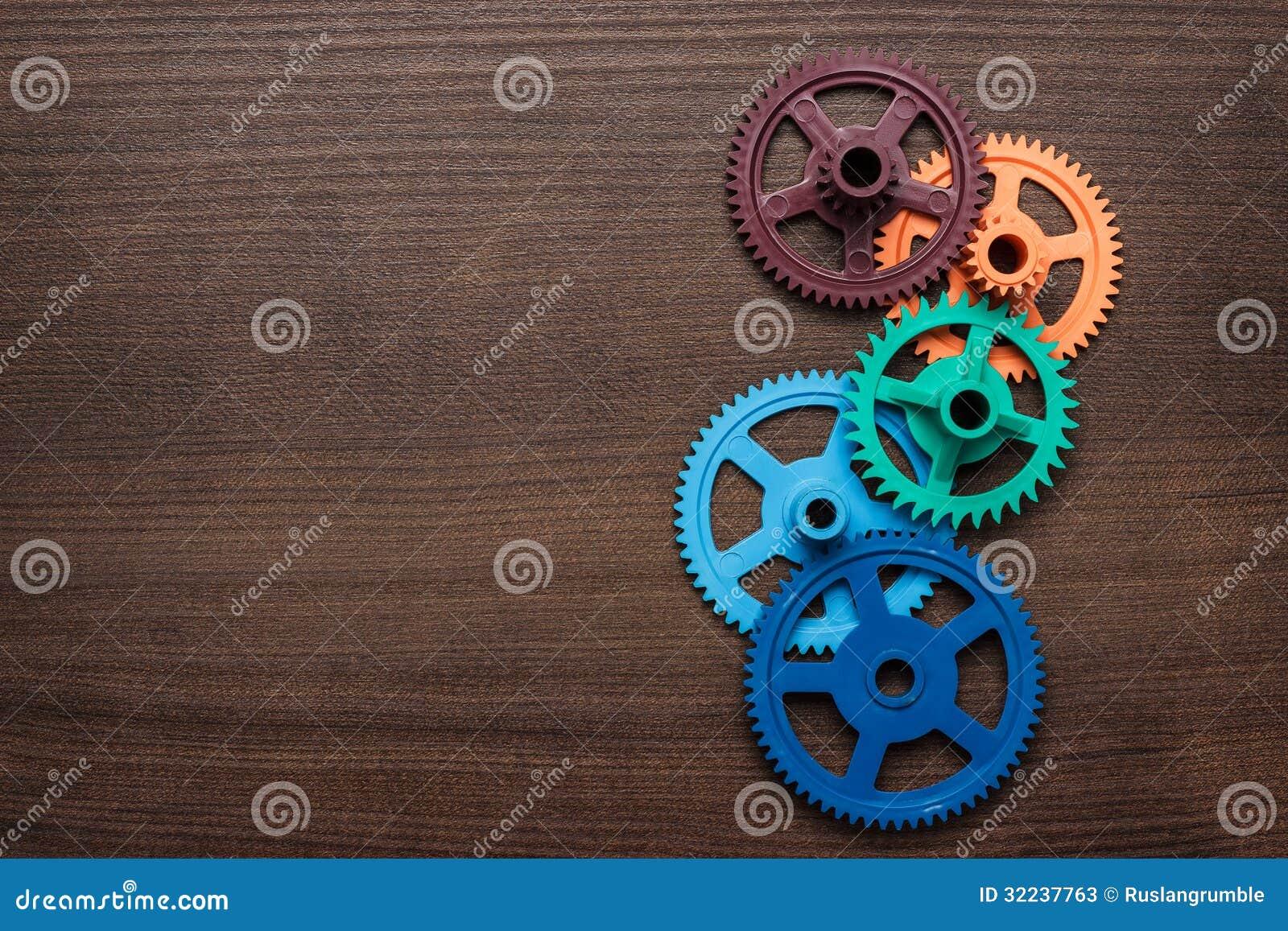 Цветастые шестерни на деревянной предпосылке