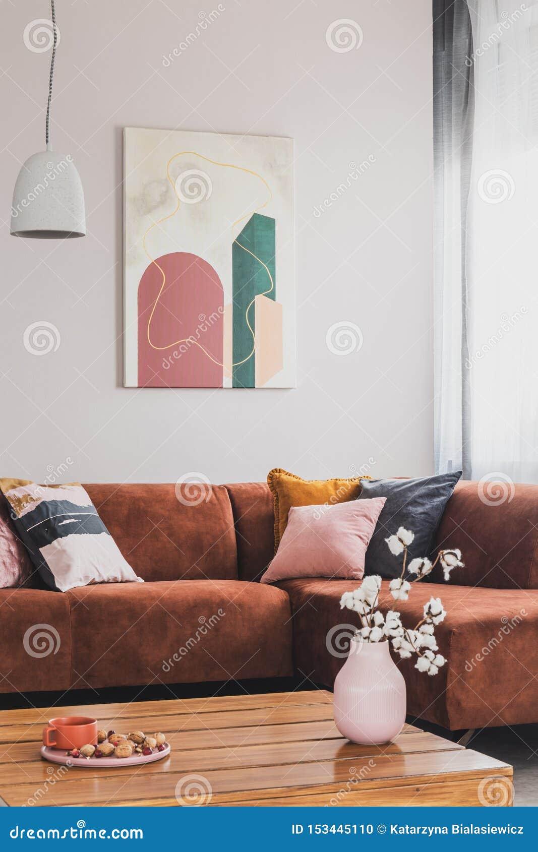 Цветки в вазе на деревянном журнальном столе в модном интерьере живущей комнаты с коричневой угловой софой с подушками и конспект