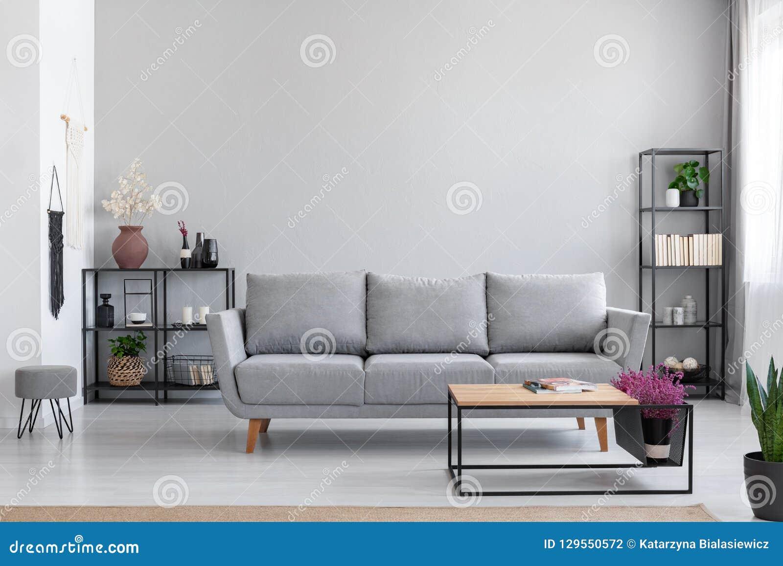 Цветки в деревянном столе перед серым settee в современной простой квартире внутренней с табуреткой