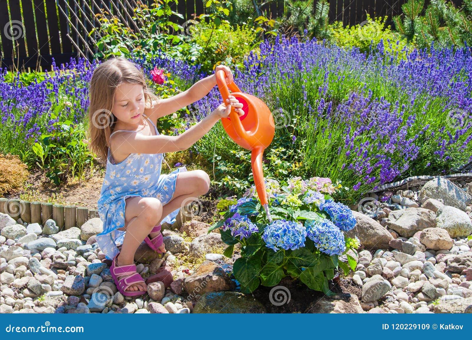 Цветки маленькой девочки моча в саде