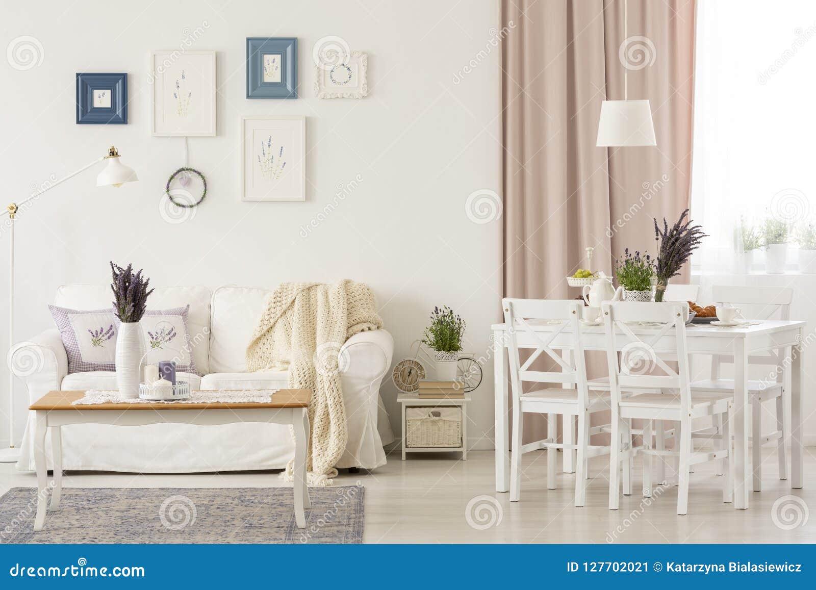 Цветки на таблице в белом интерьере живущей комнаты с пинком задрапировывают и плакаты над софой Реальное фото