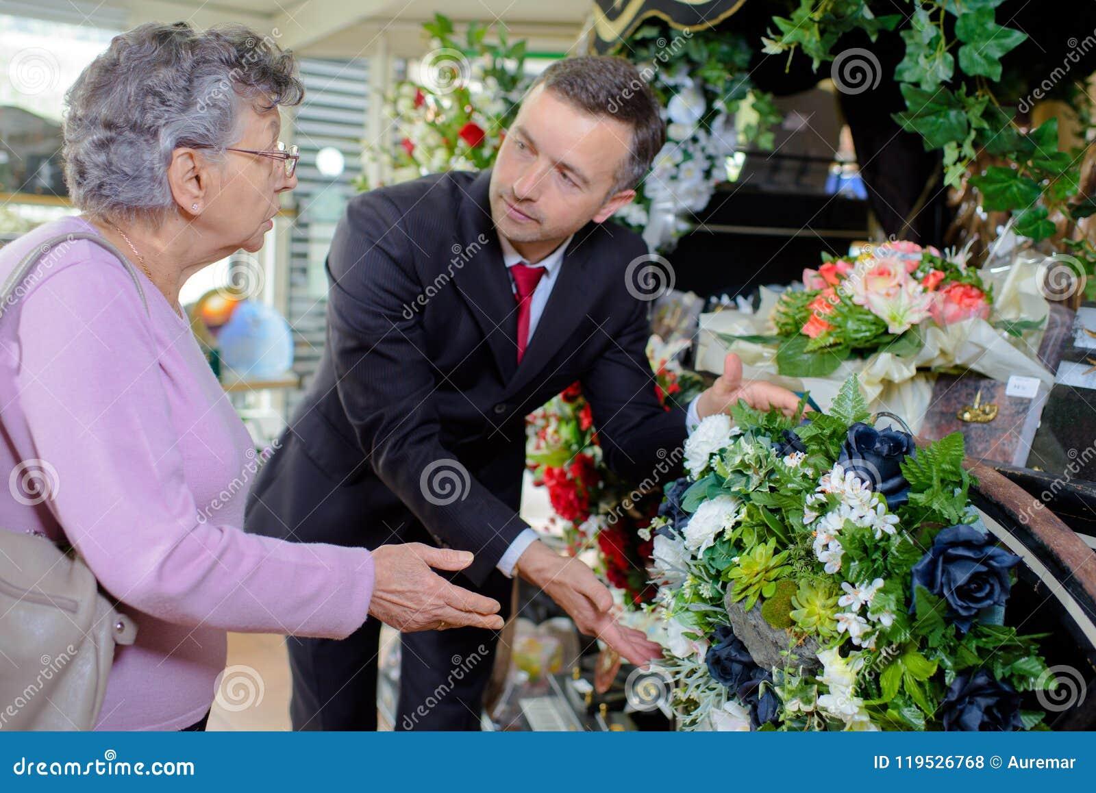 Цветки пожилой женщины покупая на похоронных услугах
