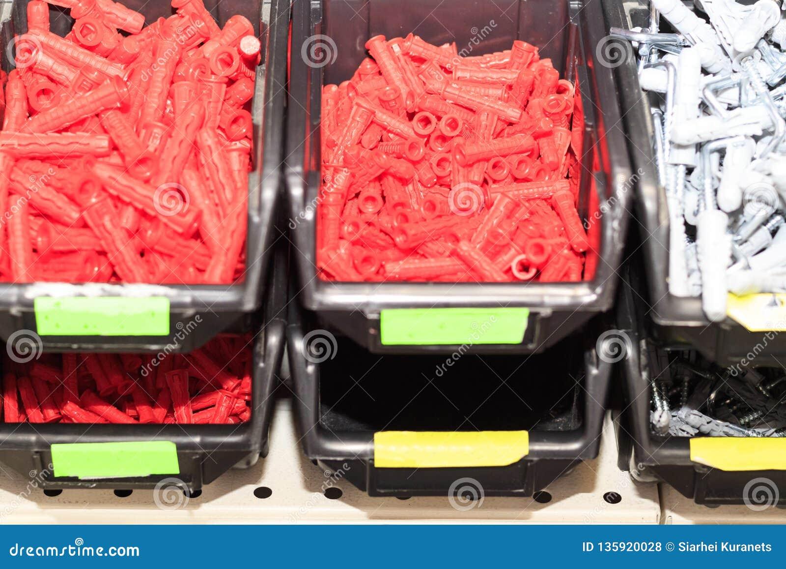 цвет винтов и шпонок красный в магазине в окне магазина, в темной коробке поле глубины отмелое