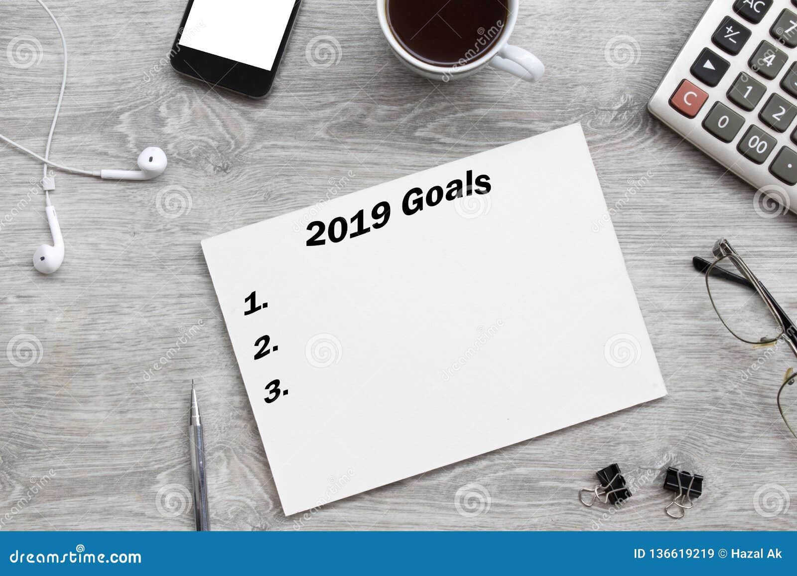 2019 целей перечисляют с бумагой, чашкой кофе сверх на серой предпосылке