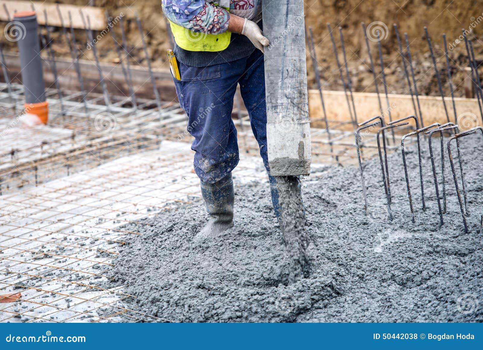 Цемент или бетон работника строительной конструкции лить с трубкой насоса