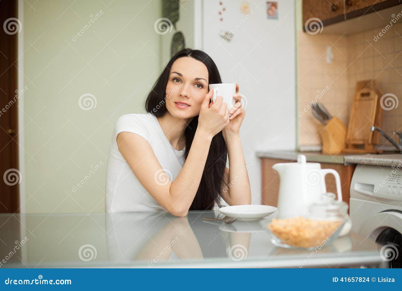Чай девушки выпивая в moring