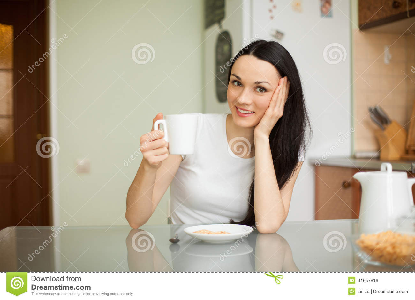 Чай девушки выпивая с печеньем в утре