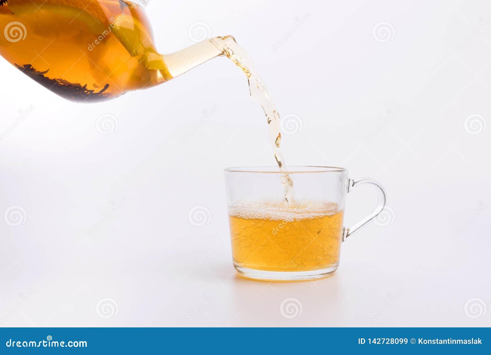 Чай лить в стеклянную чашку изолированную на белизне