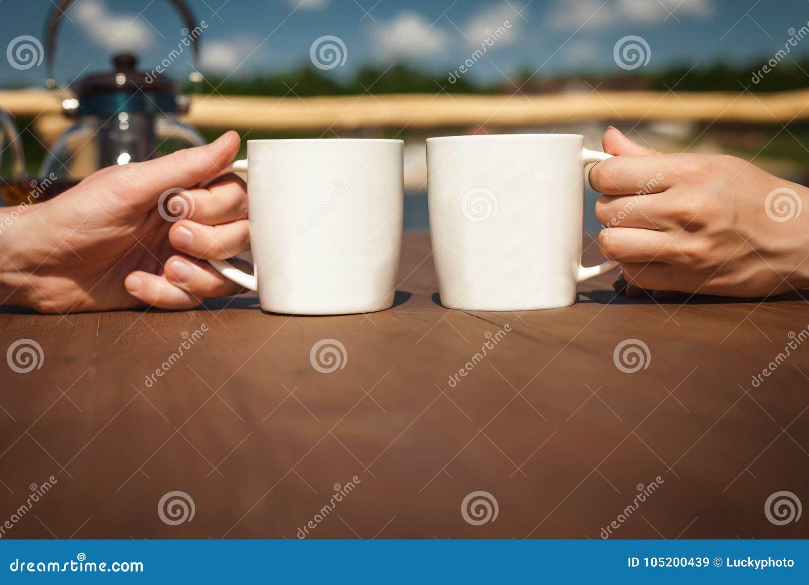 Чай мальчика и девушки отдыхая и выпивая около озера на террасе