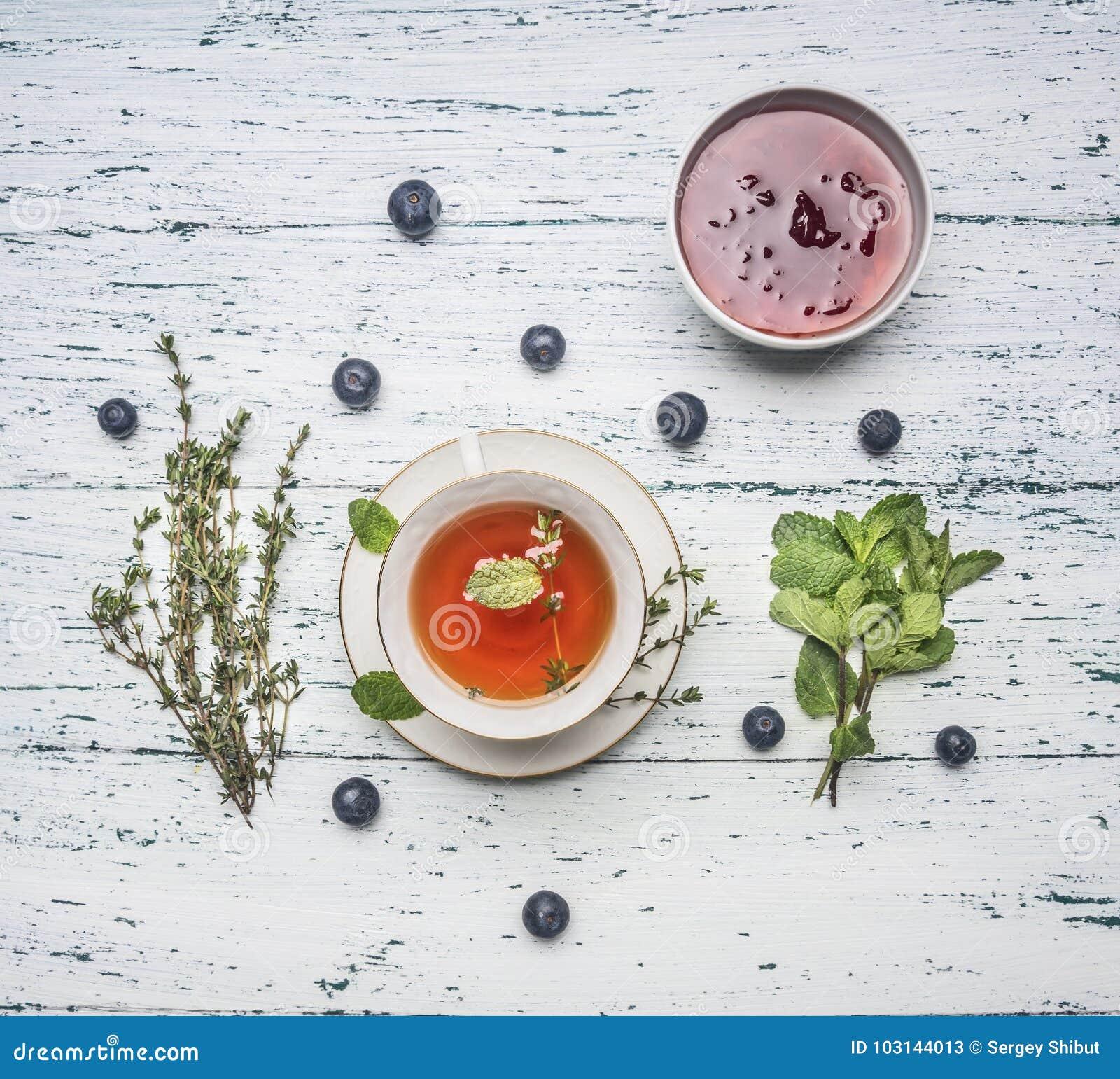 Чай целительной осени горячий травяной с ягодами, тимианом и мятой, вареньем от розы, ложки, лимона отрезка, на деревенской дерев